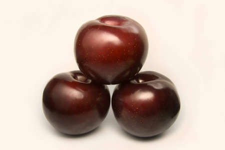 Three shiny ripe plums forming a shape of a pyramid isolated on the white background