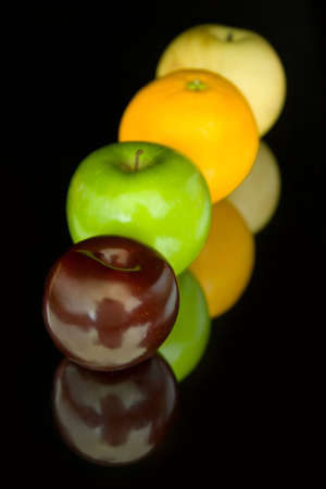Plum, green apple, orange and a pear in a line on the black background