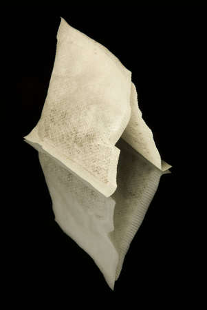 Two white standing tea bags on the black reflecting background