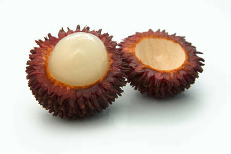 Ripe tropical fruit rambutan cut in the middle on the white background