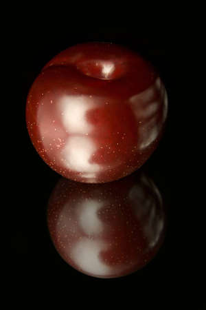 Ripe red plum with a lot of reflections on the black background