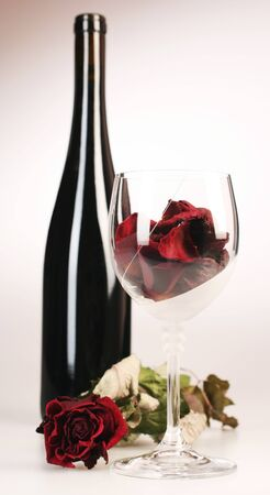 Black bottle and glass with roses photo
