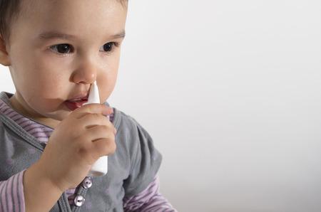 nasal drops: little girl using nasal spray - white background Stock Photo