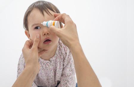 Nahaufnahme der Mutter gießt Augentropfen in die Augen ihrer Tochter Standard-Bild