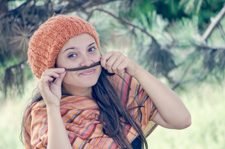 Beautiful girl with hairdo putting braids tail end like moustache photo