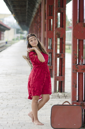 barefoot girl with suitcase waiting at the train station photo