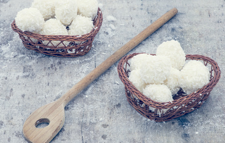 panellets: Arrangement of coconut cookies on brown baskets and wooden spoon