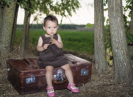 blowing dandelion: Cute little girl blowing dandelion on a suitcase outside