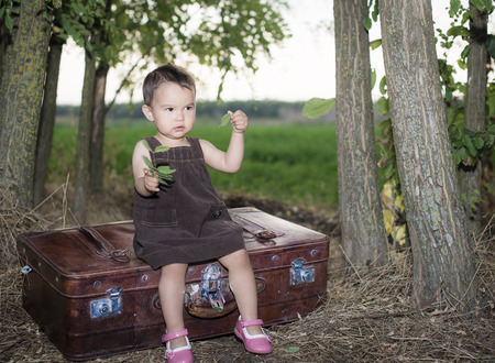 Cute little girl on a suitcase outside photo