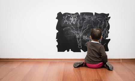 chalk writing: Toddler drawing on the blackboard Stock Photo