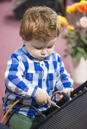 hardrock: Little boy putting a cable into a speaker