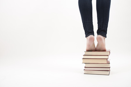 abstract academic: Woman standing on pile of books