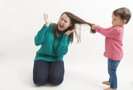 어린 소녀가 언니의 머리카락을 당긴다.