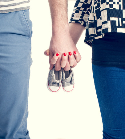 Future parents holding hands and a pair of little shoes over white background Stock fotó - 36778101