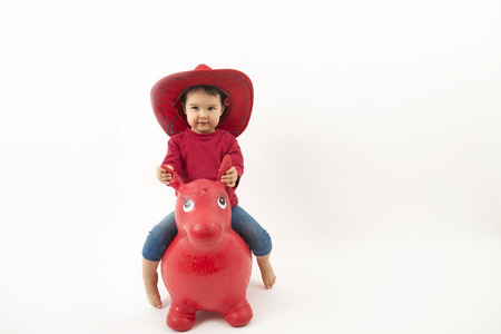Little girl with red cowboy hat riding o toy horse isolated photo