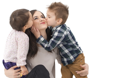 mum and baby: little girl and boy kissing their mother