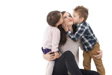 smiling mother: little girl and boy kissing their mother