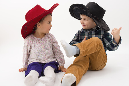 two brothers smiling wearing cowboy hats photo