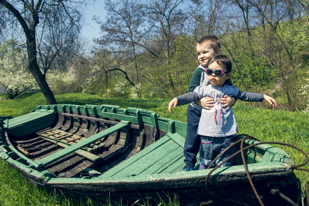 Little girl with brother having fun in an old boat