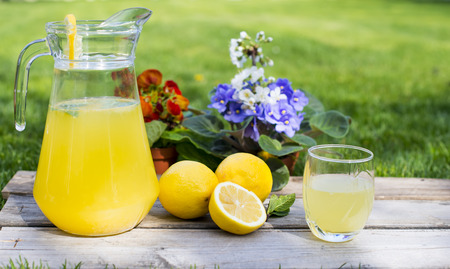 Lemonade in the jug and lemons on the table outdoor Stock fotó