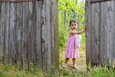 european ethnicity: Two yearold toddler girl is  opening wooden wicket gate