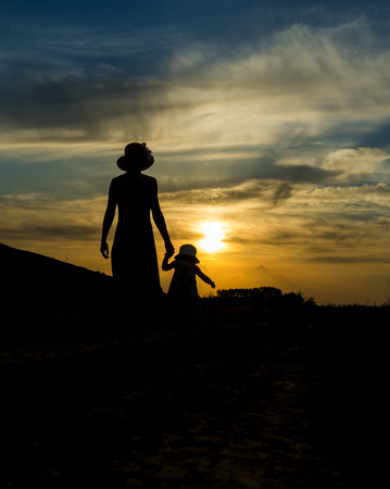 mother and daughter strolling at sunset