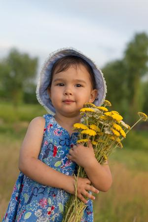 Cute little girl holding an bucket of yarrow flowers photo