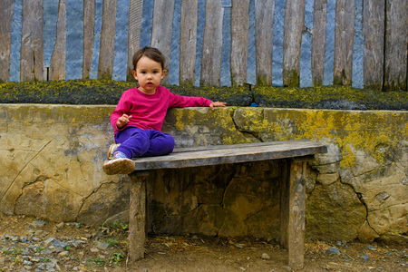 two years: Two years old  girl sitting on rustic bench