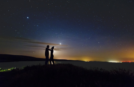 Romantic couple on sunset over the mountain