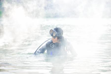 Femme plongeur dans l'eau enveloppé dans la fumée