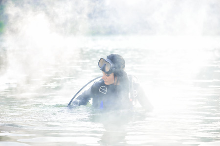 shrouded: Woman diver in water shrouded in smoke Stock Photo