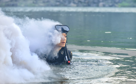 dry suit: Woman diver in water shrouded in smoke Stock Photo