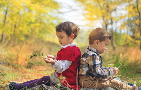 girl in nature: Two little kids playing he loves me or not Stock Photo