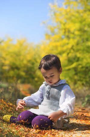 folliage: little girl sitting in folliage in autumn Stock Photo