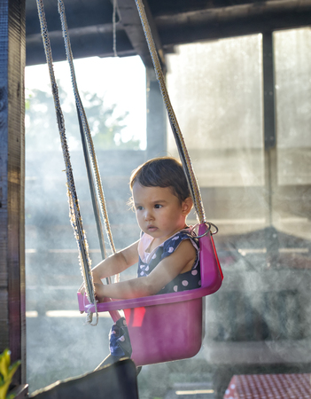 surrounded: Little girl on a swing surrounded by smoke in the garden