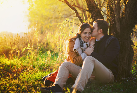 jungle boy: Young couple sitting and kissing near the tree in the forest Stock Photo