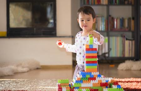 Schöne lachendes kleines Kind, Brünette Mädchen im Vorschulalter spielen mit bunten Blöcken auf einem Boden mit einem großen Fenster zu Hause oder im Kindergarten in einem sonnigen Wohnzimmer
