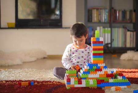 Bella piccolo bambino che ride, ragazza bruna di età prescolare giocare con blocchi colorati seduto su un pavimento in una stanza soleggiata con una grande finestra a casa o all'asilo