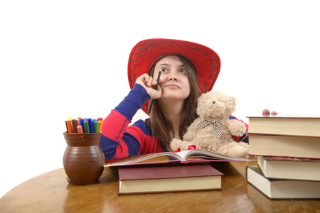 meditative: young meditative girl with red hat and her teddy bear at the table with books
