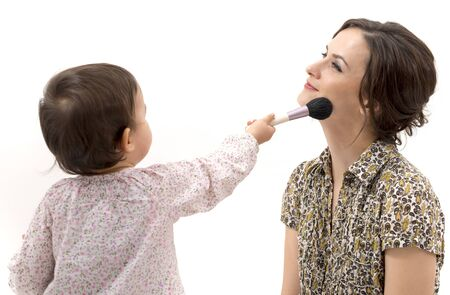 beautycare: little girl putting on the makeup to her mother Stock Photo