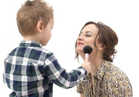 beautycare: little boy putting on the makeup to her mother