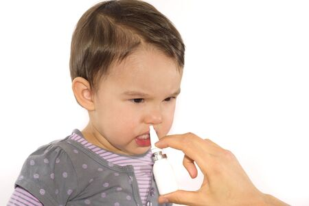 respire: parents hand of a girl applies a nasal spray