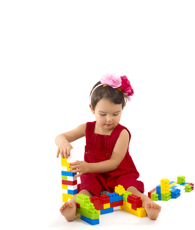 assiduous: funny child girl playing with construction set over white background