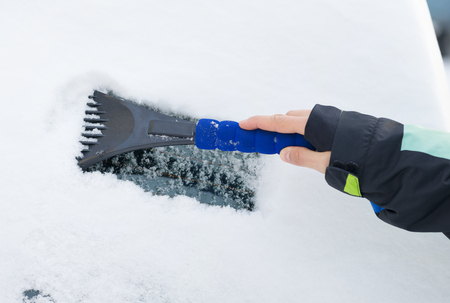 scraping: hand of a woman Scraping snow and ice from the car windscreen Stock Photo