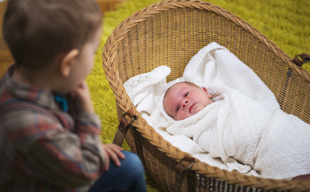 camaraderie: little boy watching over his new born baby sister