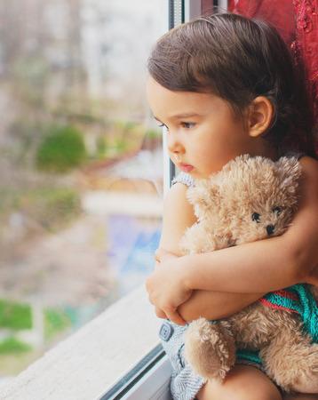 looking through window: Little girl looking through window