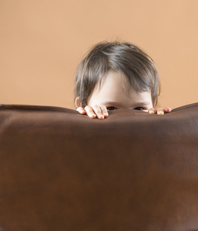 happy kid, cute girl playing and hiding behind sofa Stock Photo