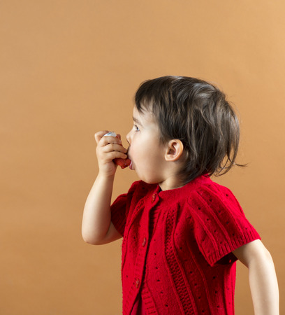 inhaler: Portrait of a girl using asthma inhaler