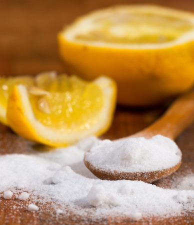 baking soda (sodium bicarbonate) in a wooden spoon and lemon Stock fotó