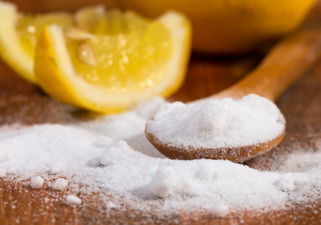 baking soda (sodium bicarbonate) in a wooden spoon and lemon 스톡 콘텐츠